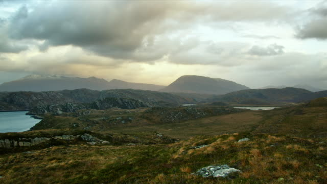 WS PAN View of highlands scenery by ocean and snowy-capped mountains with evening light and clouds / Kinlochbervie, Scotland, United Kingdom