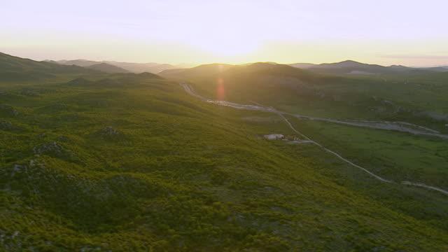 WS AERIAL View of highway and sunshine over mountain range / Split, Split Dalmatia County, Croatia