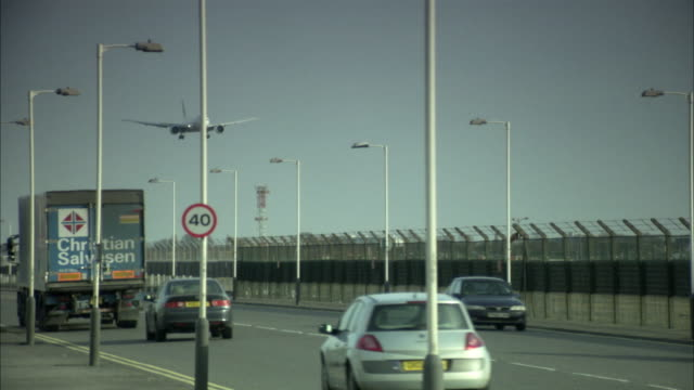 ws pan view of highway at heathrow airport, with plane landing in background / london, uk - heathrow airport stock videos and b-roll footage