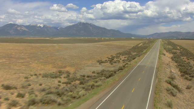 ws aerial tu view of highway leading to rio grande gorge bridge with car driving in taos county / new mexico, united states - new mexico stock videos & royalty-free footage
