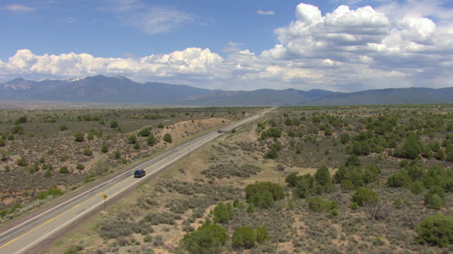 ws aerial view of highway stretching to sangre de cristo mountains in taos county / new mexico, united states - new mexico stock videos & royalty-free footage