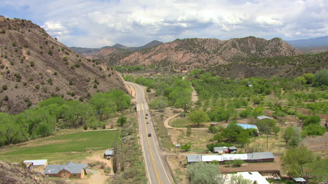 ws aerial view of highway with car in rio arriba county / new mexico, united states - hügelkette stock-videos und b-roll-filmmaterial