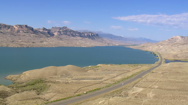 vidéos et rushes de ws aerial view of highway with river and desert mountain / wyoming, united states - wyoming