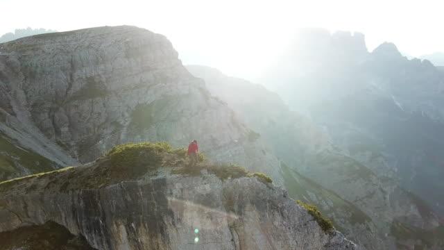 luftaufnahme der wanderer am rande einer klippe - stehen stock-videos und b-roll-filmmaterial
