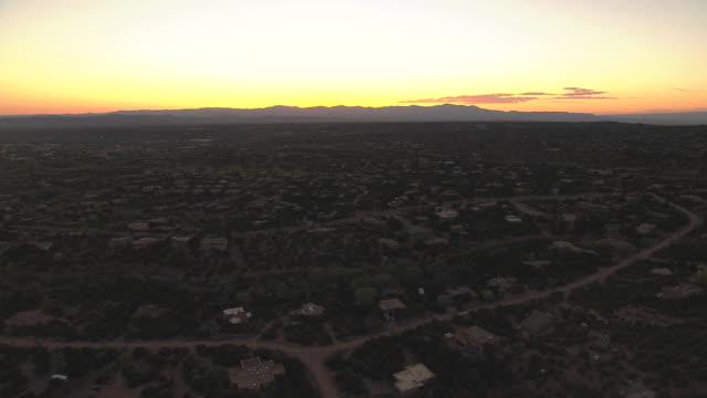 WS AERIAL View of hill to reveal city over hill with yellow sky during sunset / Santa Fe, New Mexico, United States