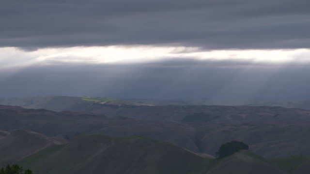 View of hills around Hawkes Bay seen from Te Mata Peak with sunlight shining through cloud cover