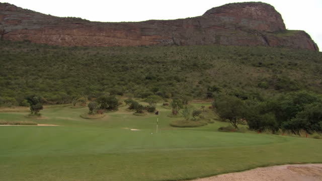 vidéos et rushes de ws view of hole marked by flag on golf course, legend golf and safari resort, waterberg / limpopo, south africa - balle de golf