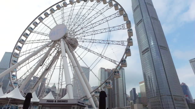 ws tu pan view of hong kong observation wheel, international finance centre in background / hong kong, china  - wheel stock videos and b-roll footage