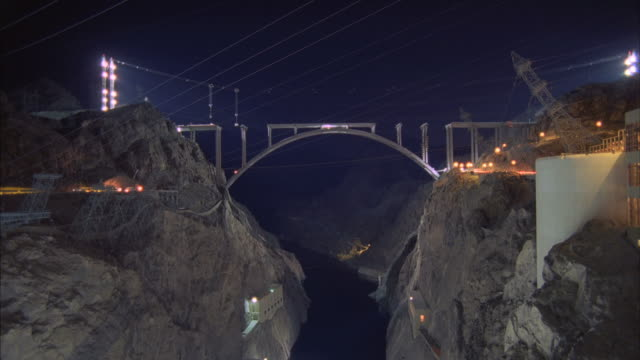 vídeos de stock, filmes e b-roll de  ws t/l view of hoover dam near bridge under construction at night / mojave, california, usa - ponte
