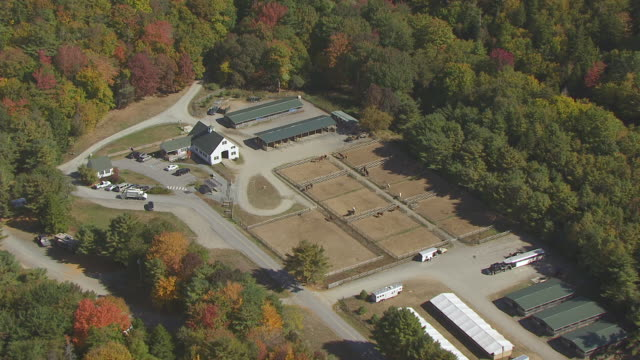 ws aerial pov view of horse stable surrounded by trees / mount desert, maine, united states - pferdestall stock-videos und b-roll-filmmaterial