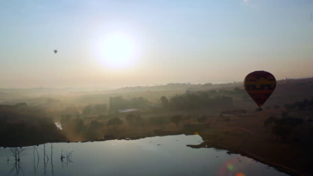 stockvideo's en b-roll-footage met ws pan view of  hot air balloon flight at sunrise over gauteng province / magaliesberg , gauteng, south africa - gauteng provincie