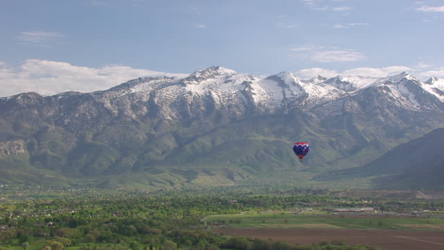 WS AERIAL View of hot air balloon with Wasatch mountain range / American Fork, Utah, United States
