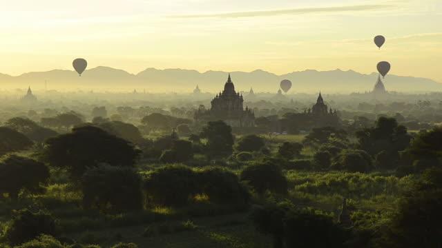 ws view of hot air balloons float above bagans temples at sunrise / bagan, mandalay division, myanmar - pagoda stock videos & royalty-free footage