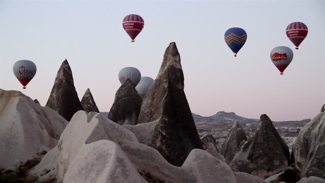 vídeos de stock, filmes e b-roll de ws t/l view of hot air balloons flying between rocks over cappadocia / goremel, turkey - capadócia