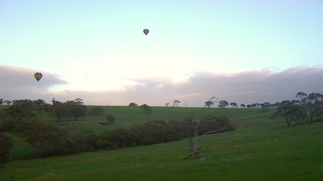 WS AERIAL View of hot air balloons flying over landscape / Kings Cliff, New South Wales, Australia