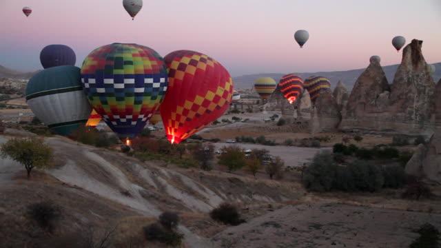 WS View of Hot Air Balloons Rise over Goreme Town in Cappadocia / Goremel, Turkey
