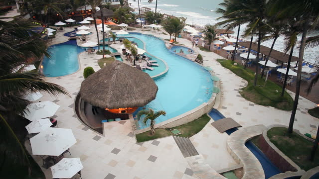 WS HA View of hotel pool area with coconut trees waving in breeze / Natal, Rio Grande Do Norte, Brazil