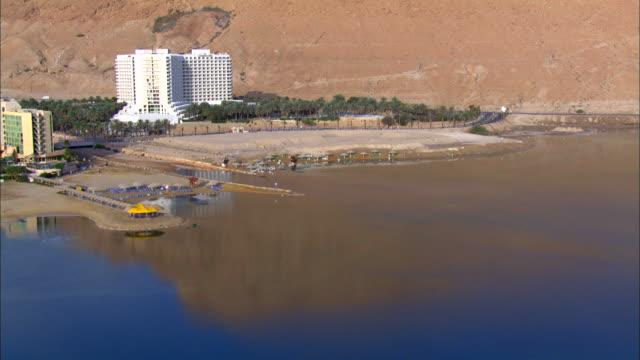 aerial  ws view of hotels in city near dead sea / ein boqeq, sourn judea desert, israel - 聖地パレスチナ点の映像素材/bロール