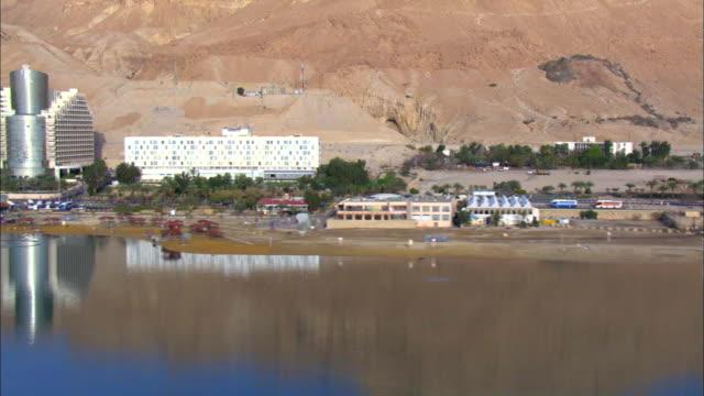 aerail ws pan view of hotels in city near dead sea / ein boqeq, sourn judea desert, israel - 聖地パレスチナ点の映像素材/bロール