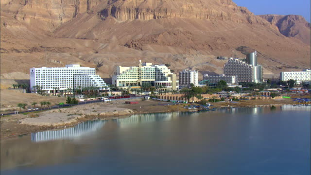aerial ws pan view of hotels in city near dead sea / ein boqeq, sourn judea desert, israel - 聖地パレスチナ点の映像素材/bロール
