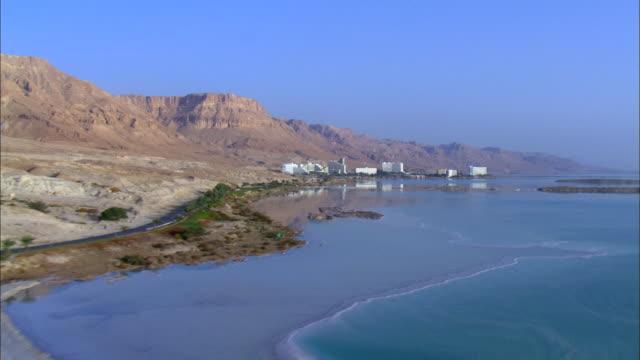 aerial ws ts  view of hotels in city near dead sea / ein boqeq, sourn judea desert, israel - 聖地パレスチナ点の映像素材/bロール
