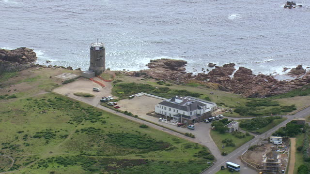 WS AERIAL View of house and tower near coastline / Jersey, Channel Isles