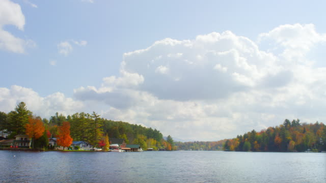 WS View of houses and boathouse along lake edge with puffy clouds / Saranac Lake, New York, United States