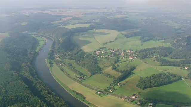vídeos de stock, filmes e b-roll de ws aerial view of houses and farm field near elbe river / germany - rio elbe