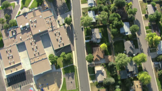 MS AERIAL View of houses and streetscape with parked cars, playground and school / Denver, Colorado, United States