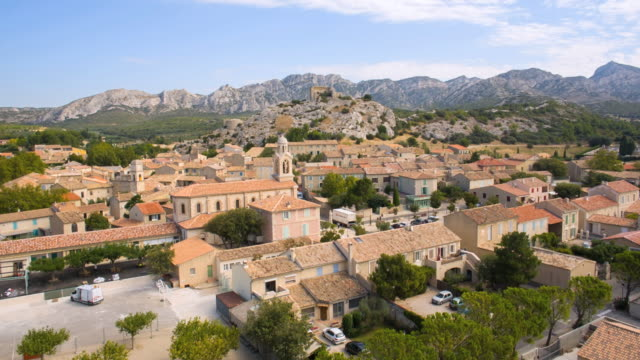 WS AERIAL PAN View of houses at village with mountain / Aureille, Provence, France