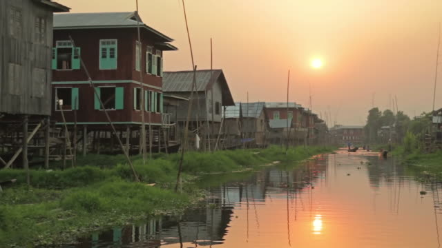 ws pov view of houses constructed on inle lake at sunset / inle lake, shan state, myanmar   - shan state stock videos & royalty-free footage