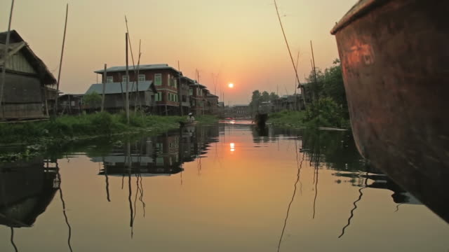 ws la pov view of houses constructed on inle lake at sunset / inle lake, shan state, myanmar   - shan state stock videos & royalty-free footage