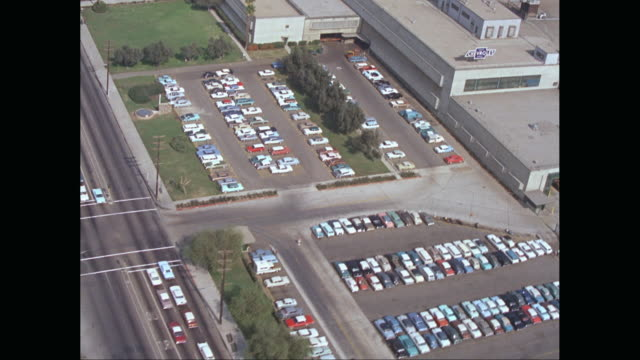 WS AERIAL POV View of houses in town, cars parked outside of automobile industry / United States