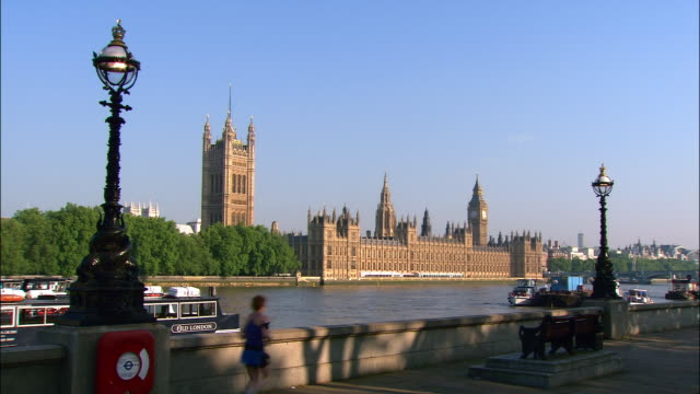 view of houses of parliament on bank of thames / people jogging, cycling, and walking along south bank / london, england - victoria tower stock videos & royalty-free footage
