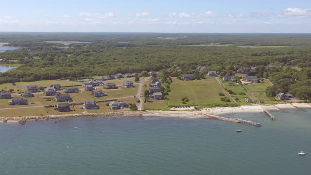 ws aerial pov view of houses with tree area near coastline / new bedford, massachusetts, united states  - new bedford stock videos & royalty-free footage