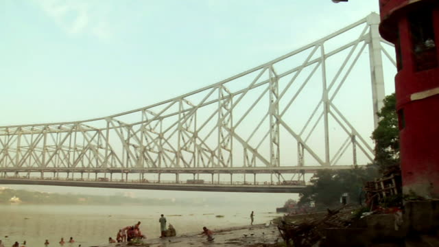 MS PAN View of Howrah bridge over hooghly river and people bathing near riverside  / Kolkata, west Bengal, India