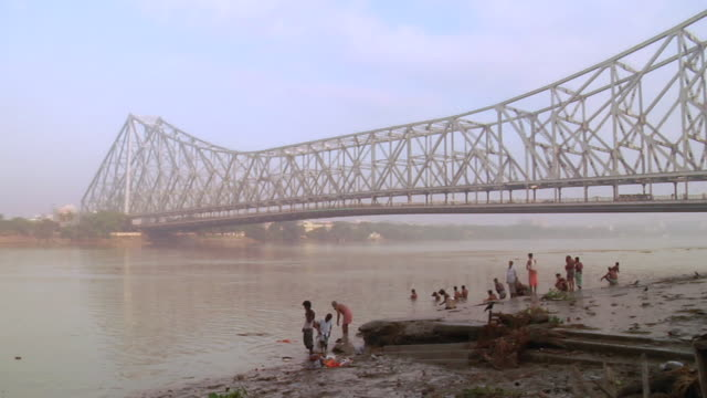 MS View of Howrah bridge over hooghly river and people bathing near riverside  / Kolkata, west Bengal, India