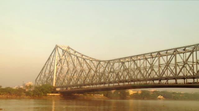ms view of howrah bridge over hooghly river  / kolkata, west bengal, india - howrabron bildbanksvideor och videomaterial från bakom kulisserna