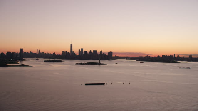 vídeos de stock, filmes e b-roll de aerial ms view of hudson river with statue of liberty and city on a distance at early morning / new york city  - porto de nova york