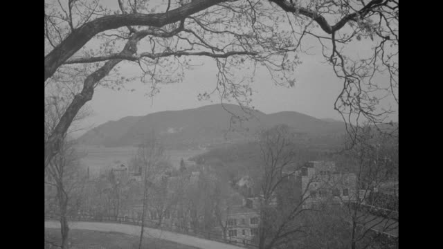 view of hudson valley seen though budding branches with us military academy cadets marching in formation below; buildings with crenellated towers on... - ウェストポイント点の映像素材/bロール