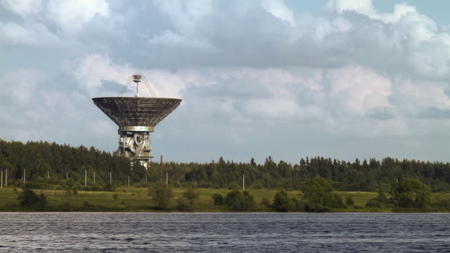 ws t/l view of huge satellite dish aimed at sky, stands near river bank / kaljazin, russia - mast stock videos & royalty-free footage