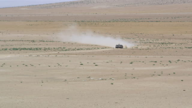 ws ts view of humvee approaching through desert / desert, jordan - 軍用輸送車点の映像素材/bロール
