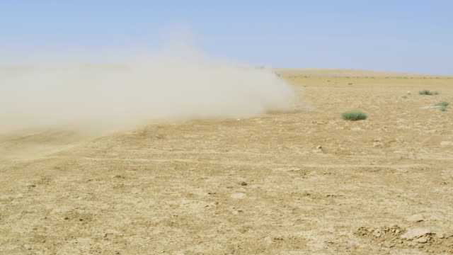 WS PAN View of Humvee driving away in Desert / Desert, Jordan