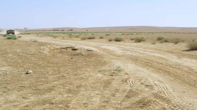 ws pan view of humvee passing on desert road and village in distance / desert, jordan - humvee stock videos & royalty-free footage