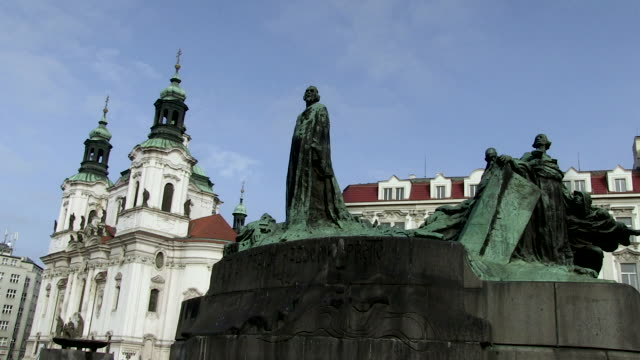 ms view of hus monument behind church st. nicolas / prague, hlavni mesto praha, czech republic - stare mesto stock videos and b-roll footage