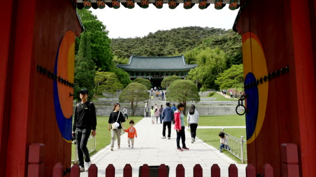 view of hyeonchungsa shrine(the place to enhance achievement of yi sunsin general) through chunguimun gate - shrine stock videos & royalty-free footage