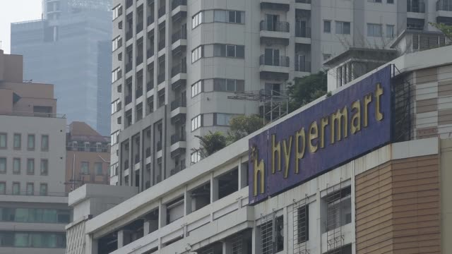 View of Hypermart signage on the side of a building Pan L R from skyscraper to hypermart signage on the side of a building Pan L R of cars parked by...