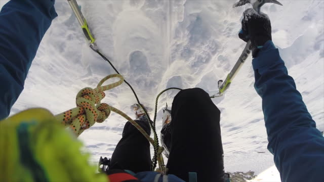 pov view of  ice axes and a man ice climbing on snow in the mountains. - deep snow stock videos & royalty-free footage
