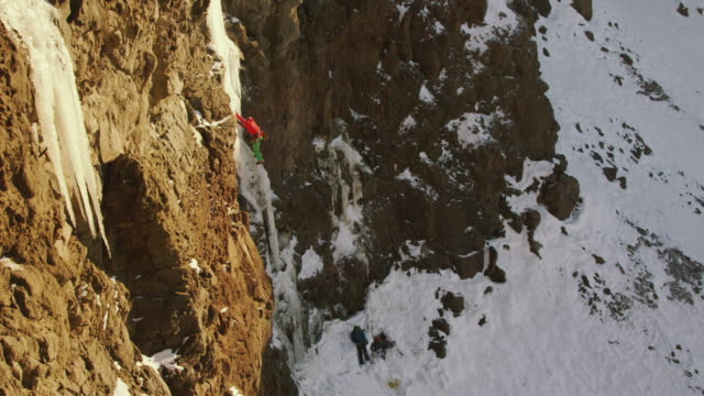 vídeos y material grabado en eventos de stock de ws pan view of ice climber going up steep pillar of ice surrounded by rock and snow with sun is setting / cody, wyoming, united states - cuerda de alpinismo