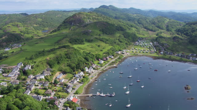 WS AERIAL PAN View of idyllic coastal village with yachts in bay revealing Sound of Jura on west coast with few boats beyond / Tayvallich, Argyll and Bute, Scotland